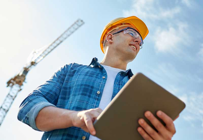 Superior Scaffolding & Insulation, Inc. Image of Construction Worker Holding Tablet in Front of Crane